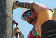 Lineman hammering on pole