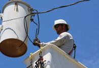 Lineman in bucket holding wires
