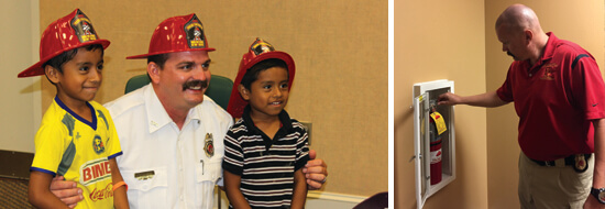 FMO posing with two boys in toy firemen hats and fire marshal checking fire extinguisher