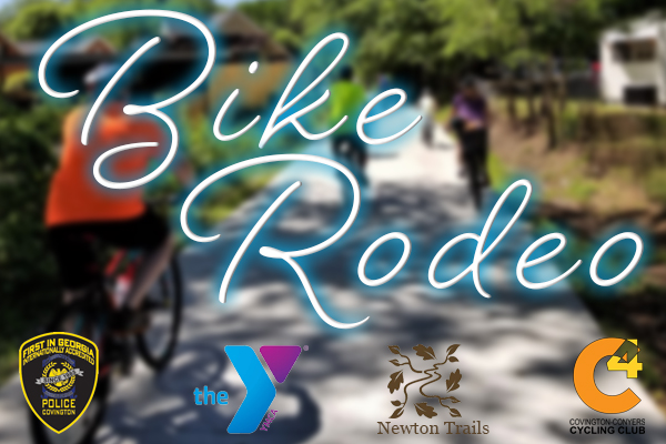 Blurry image of bike riders with glowing white and blue words Bike Rodeo