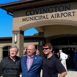 John King, Covington Airport Director, and two friends outside the airport terminal