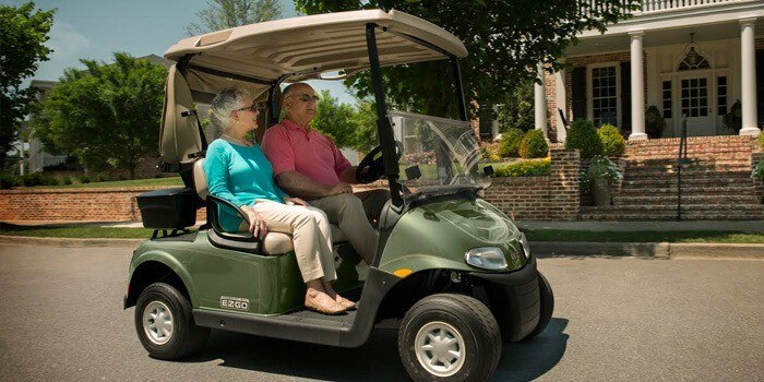Older couple driving in green EZ Go golf Cart