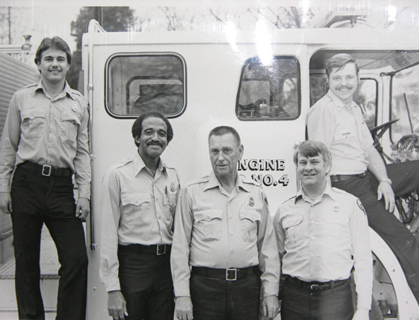 Black and white pic of 5 firefighters posed in front of 1974 firetruck